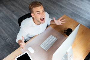 Top view of mad irritated young businessman working with computer and shouting