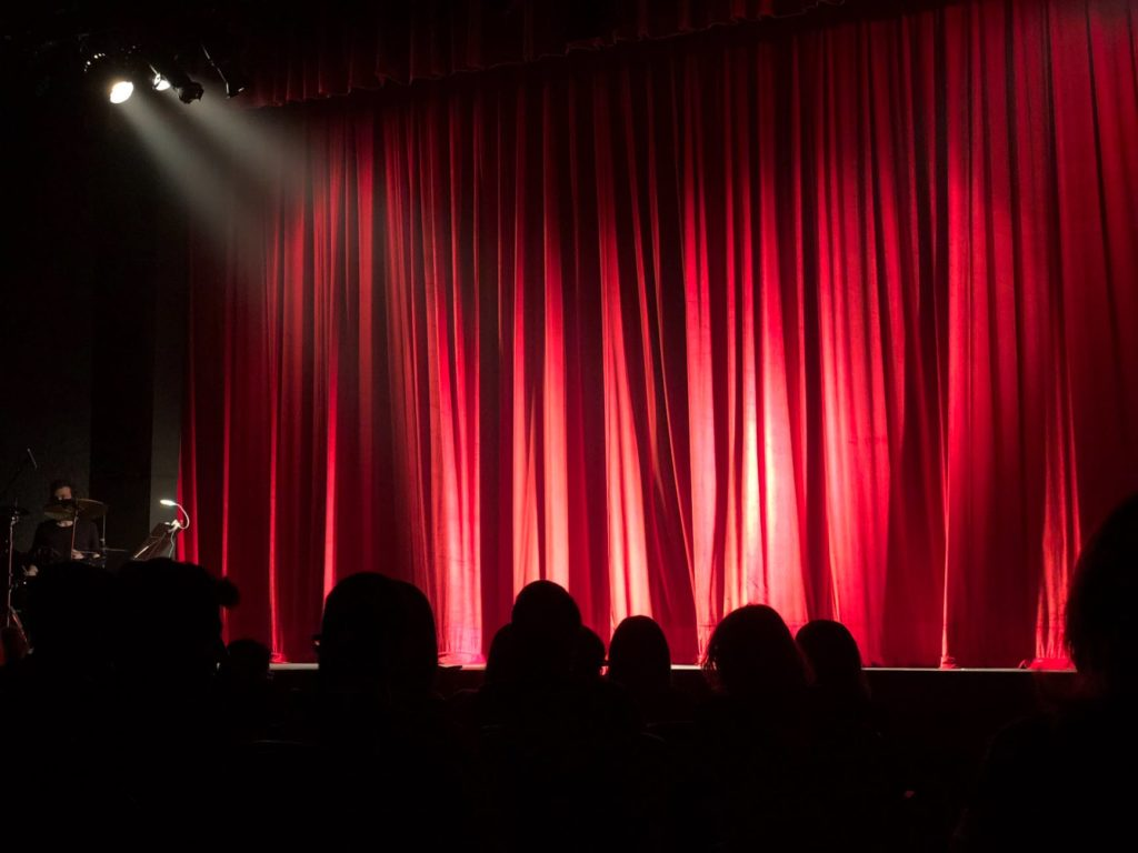 audience in front of theater red curtain