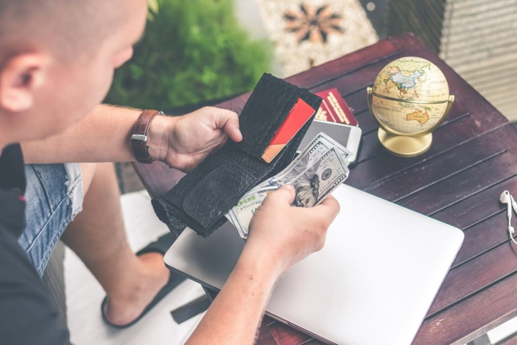 Man Pulling Cash Out Of Wallet
