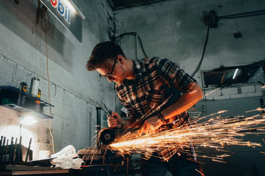 man grinding metal with sparks flying