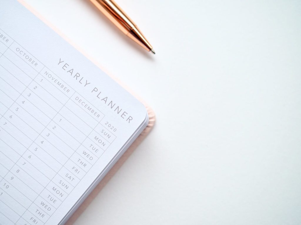 yearly planner and gold pen on white desk
