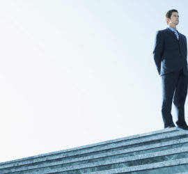 man in business suit standing on platform