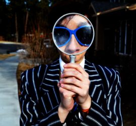 man holding magnifying glass with blue sunglasses on