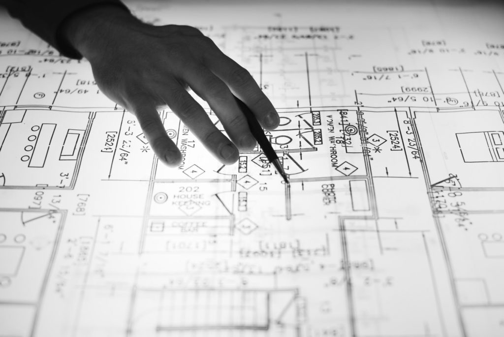 black and white photo of someone working on a blueprint