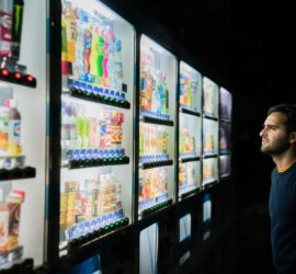 man in front of vending machines at night