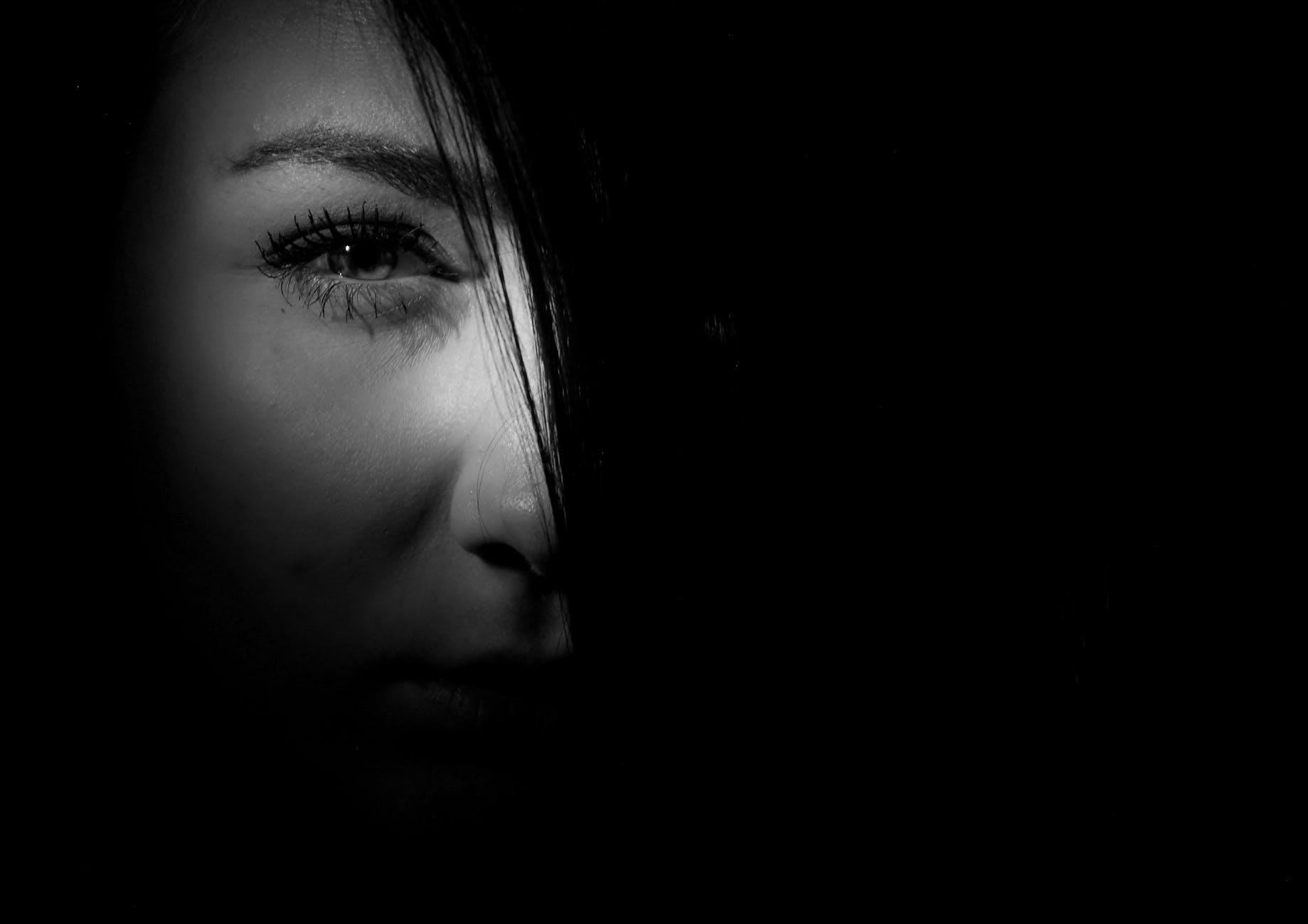 black and white photo of a woman with half her face lit up