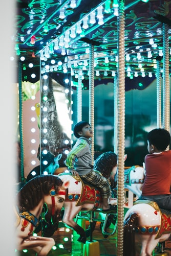 small asian boy on blue lighted carousel