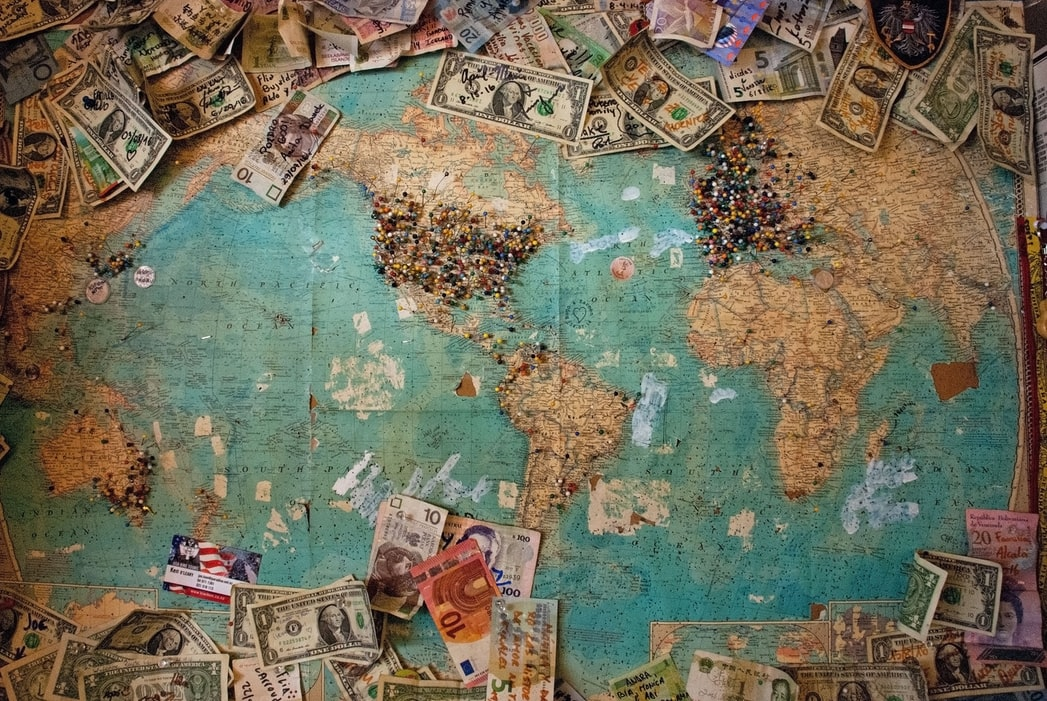 world map with different world currencies around it