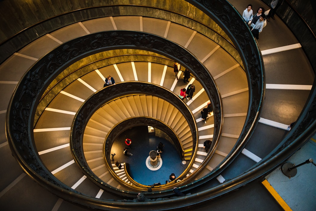 staircase winding down with people on it