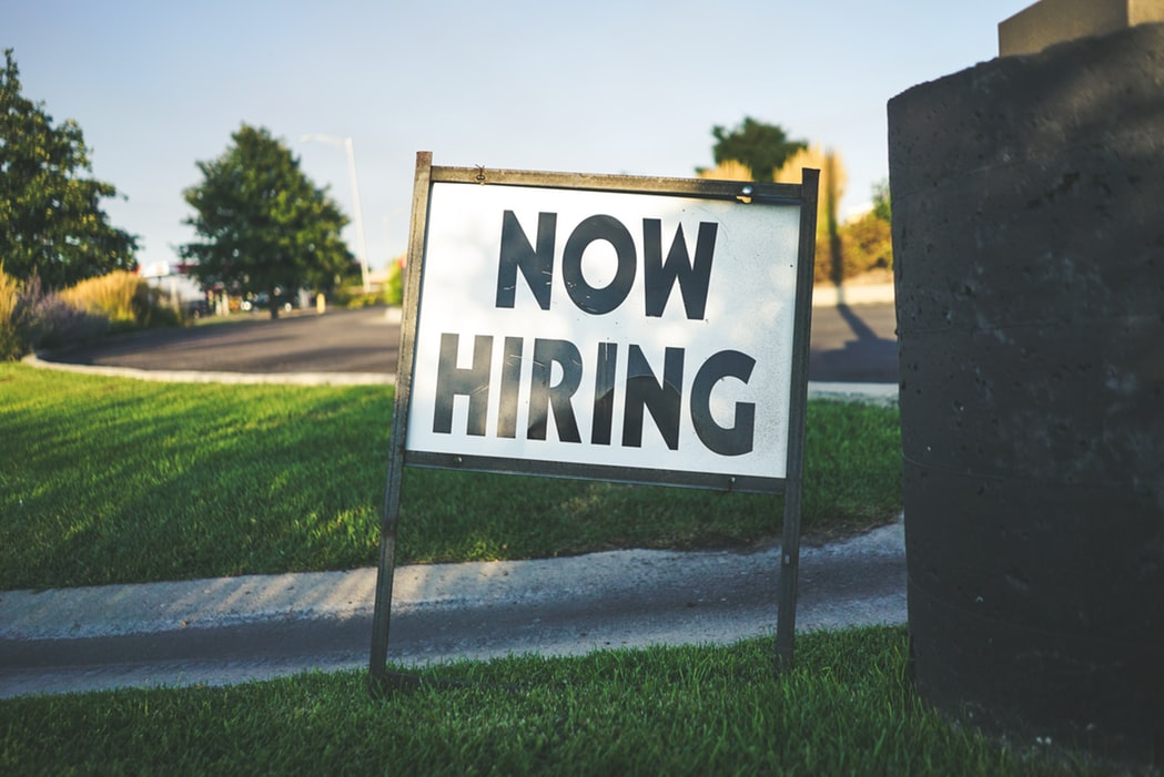 now hiring sign on green grass