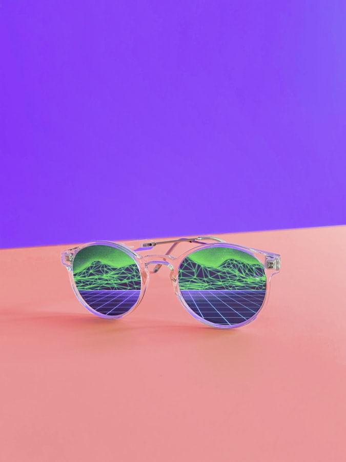 sunglasses with mountains reflected on purple and pink background