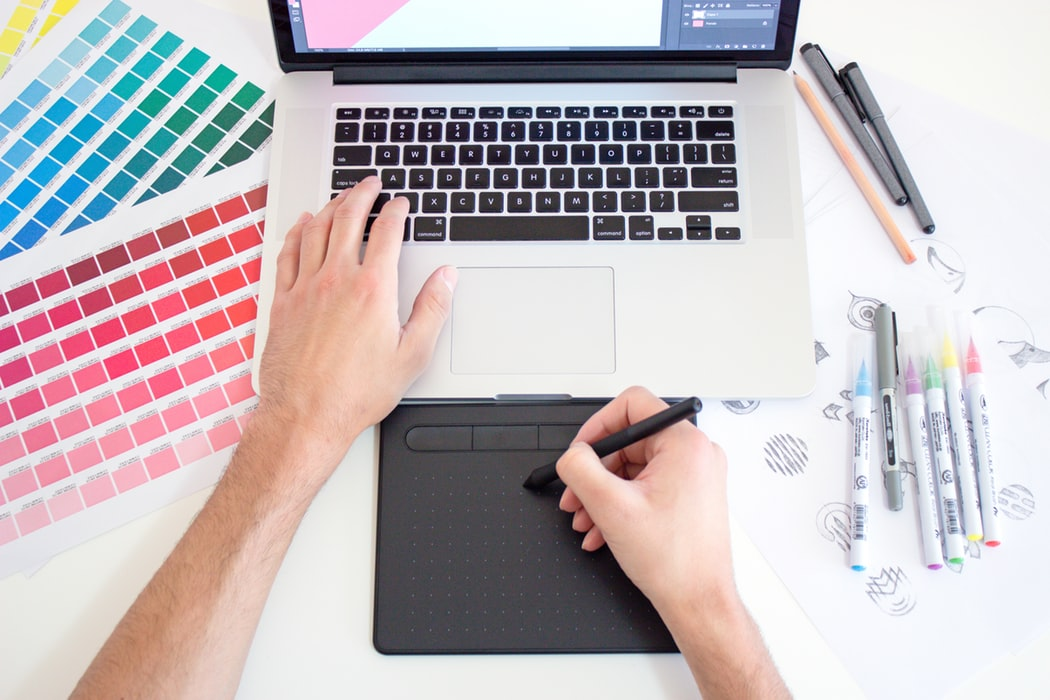 web designer with color palettes and computer in front of him