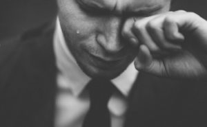 man in suit crying