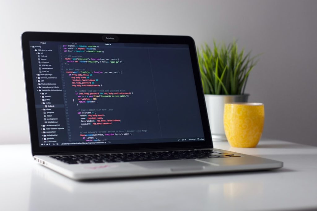 code on a laptop screen on a white desk with plant and yellow cup