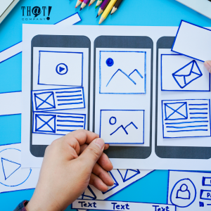 User Experience And User Interface | A Hand Placing Some Paper Cut-Outs Showing A Mobile Preview Design Of An Application