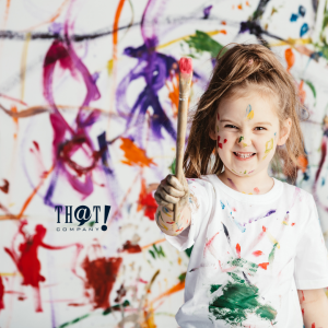 Creative Marketer | A Kid Smiling While Holding A Paint Brush With Paint All Over the Wall And Her Body