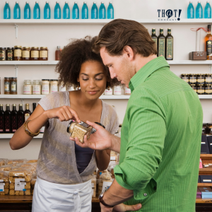 Responsibility | A Girl Explaining Something In A Product To A Man While Pointing At The Products Label