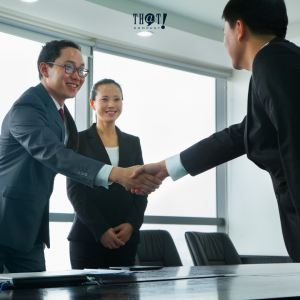 Respect | A Man Shaking Hands With Another Man Beside A Girl In A Conference Room
